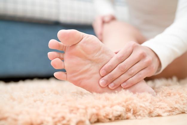 Las mujeres con dolor en el tobillo del pie tocan su pie doloroso, el concepto de atención médica y medicina