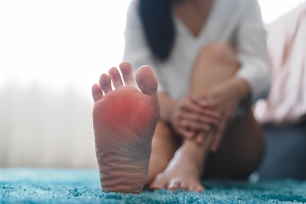 Las mujeres con dolor en el tobillo del pie tocan su pie doloroso, cuidado de la salud y concepto de medicina