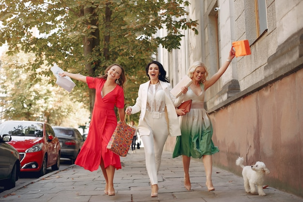Mujeres elegantes con bolsas de compras en una ciudad