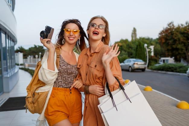 Mujeres elegantes después de salir de viaje y compras posando al aire libre cerca del aeropuerto