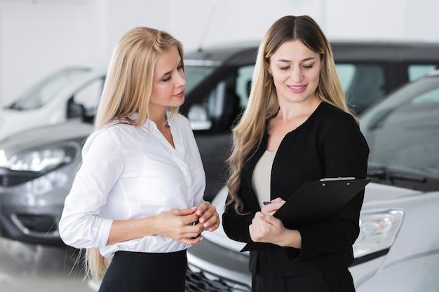 Mujeres elegantes discutiendo en la sala de exposición de automóviles