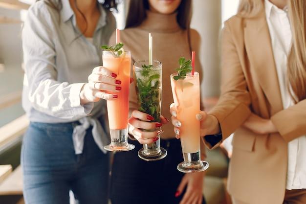 Mujeres elegantes de pie en un café y bebiendo un cóctel