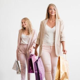 Mujeres elegantes posando con bolsas de compras