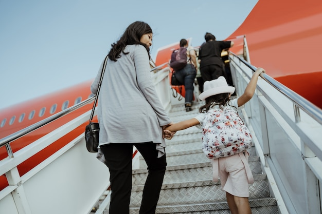 Las mujeres embarazadas asiáticas y sus hijas suben las escaleras del avión