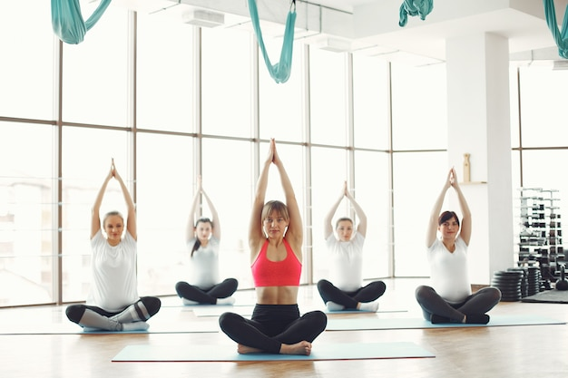 Mujeres embarazadas haciendo yoga con un entrenador