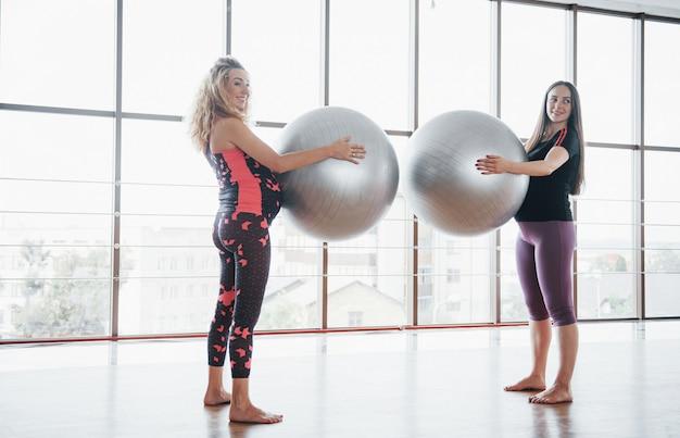 Mujeres embarazadas jóvenes de pie y sosteniendo una bala para hacer ejercicio.