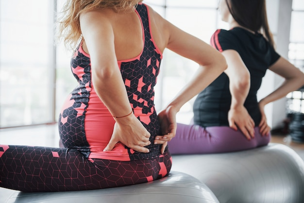 Mujeres embarazadas jóvenes sentados en la pelota para ejercicios en el gimnasio