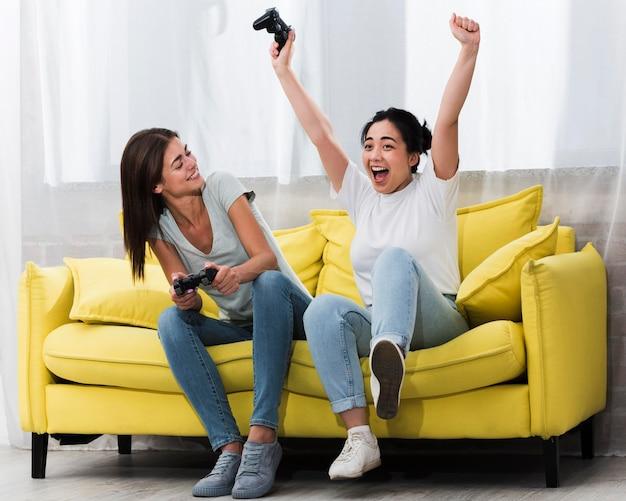 Mujeres emocionadas en casa jugando videojuegos juntos