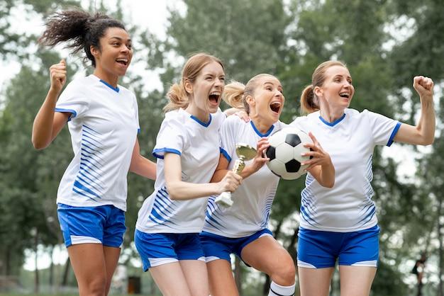 Mujeres emocionadas con copa y bola