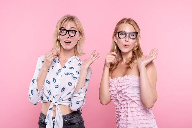 Mujeres emocionadas en la fiesta tomando fotos con máscaras