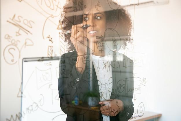 Mujeres empresarias bastante jóvenes escribiendo sobre placa de vidrio. gerente de sexo femenino afroamericano experimentado confiado que sostiene el marcador y que sonríe en el sitio de la oficina. concepto de estrategia, negocios y gestión