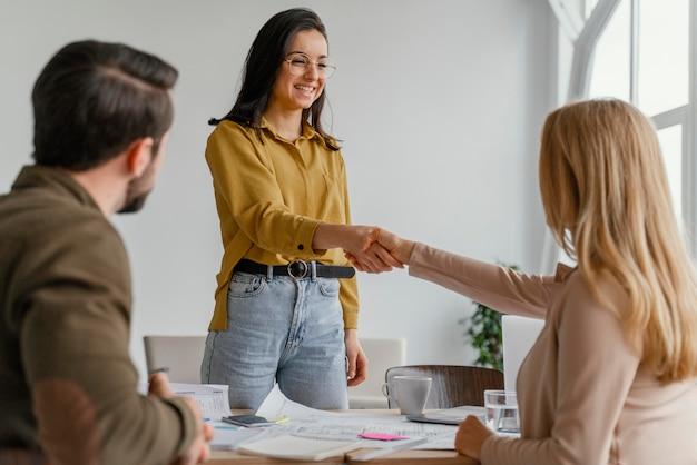 Mujeres empresarias dándose la mano en el trabajo