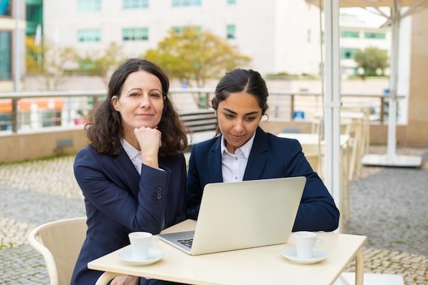 Mujeres empresarias felices con laptop en café al aire libre