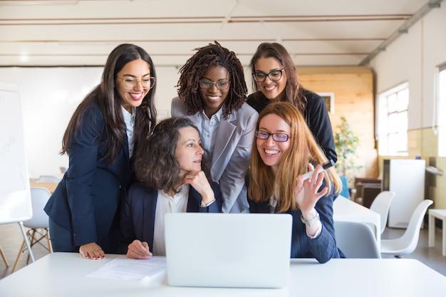 Mujeres empresarias felices trabajando con laptop