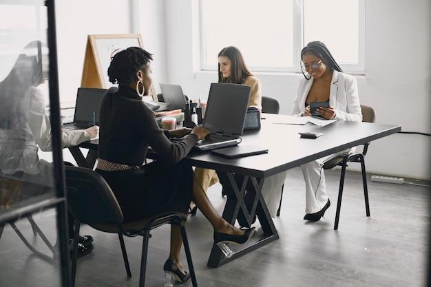 Mujeres empresarias multiculturales en reunión de grupo.