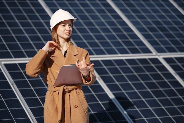 Mujeres empresarias que trabajan en el control de equipos en la planta de energía solar. con lista de verificación de tableta, mujer que trabaja en exteriores con energía solar.