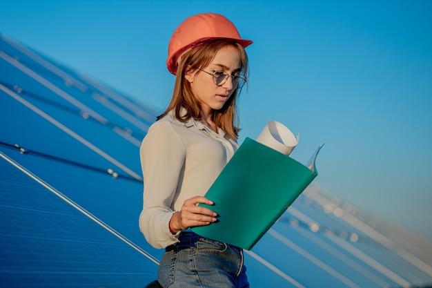 Mujeres empresarias que trabajan en el control de equipos en la planta de energía solar con lista de verificación de tableta