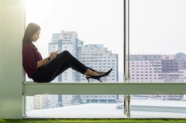 Mujeres empresarias que usan el teléfono inteligente en la oficina creativa moderna