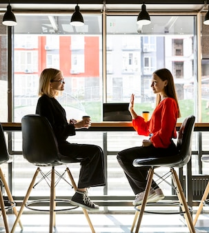 Mujeres empresarias que utilizan el lenguaje de señas en el trabajo para hablar entre sí