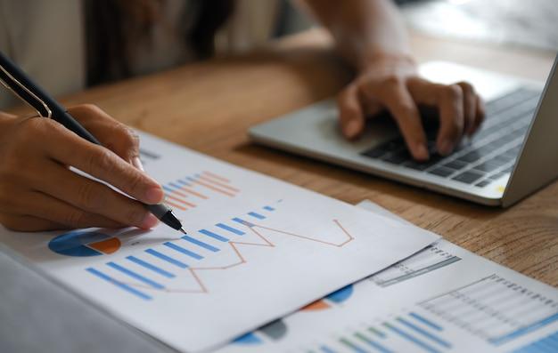 Mujeres empresarias señalan con el lápiz el gráfico de datos y usan la computadora portátil para trabajar.