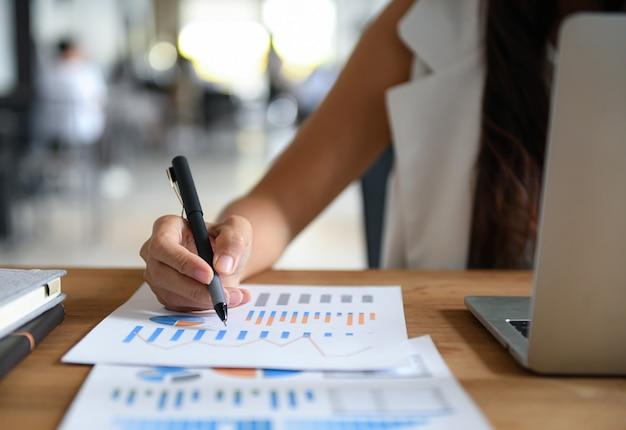 Mujeres empresarias señalaron con el bolígrafo el gráfico de datos para el análisis. gráfico, computadora portátil puesta en el escritorio de la oficina.