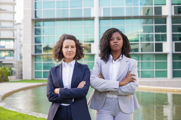 Mujeres empresarias serias seguras posando con los brazos cruzados