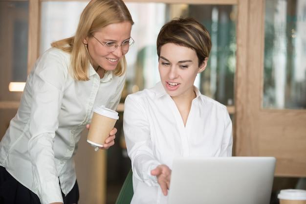 Mujeres empresarias sonrientes discutiendo buen resultado de proyecto en línea mirando portátil