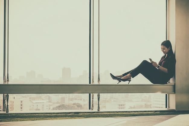 Mujeres empresarias usando el teléfono inteligente en la moderna oficina creativa.