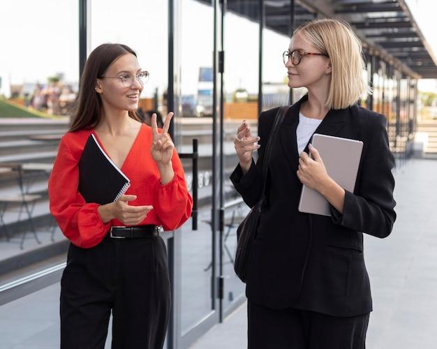 Mujeres empresarias utilizando lenguaje de señas fuera