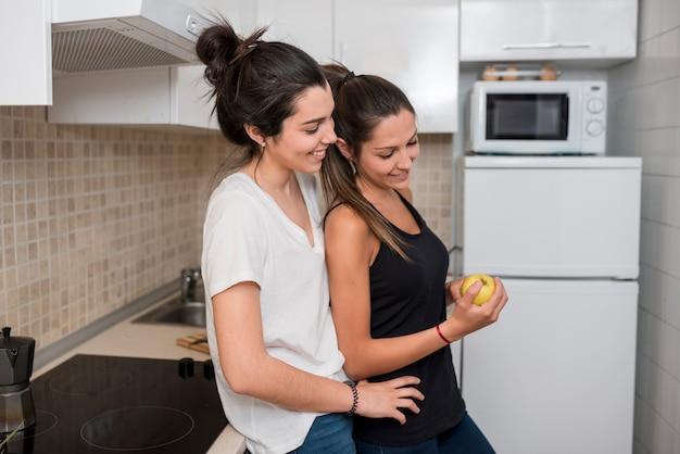 Mujeres enamoradas abrazándose en la cocina