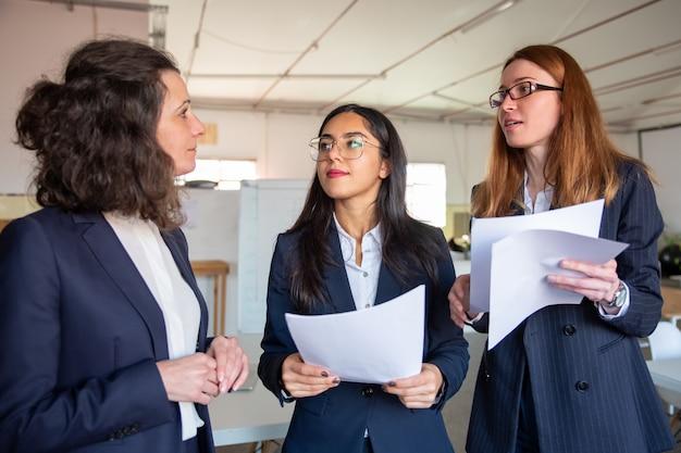 Mujeres enfocadas con documentos haciendo preguntas a un compañero de trabajo maduro