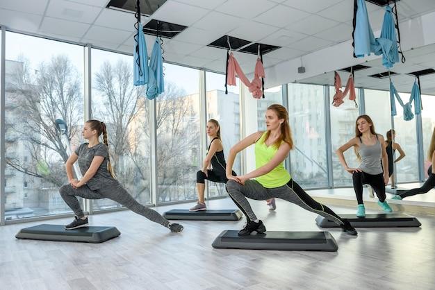 Mujeres entrenando en el gimnasio haciendo ejercicios de estiramiento
