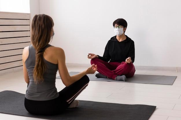 Mujeres entrenando juntas después del coronavirus con máscaras médicas