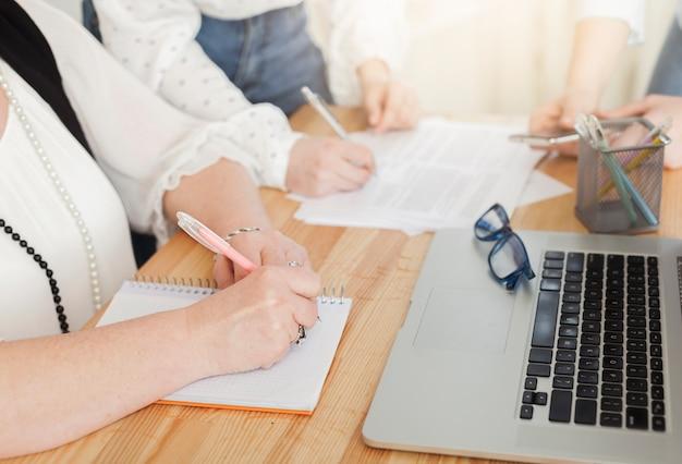 Mujeres escribiendo en cuadernos y computadoras portátiles