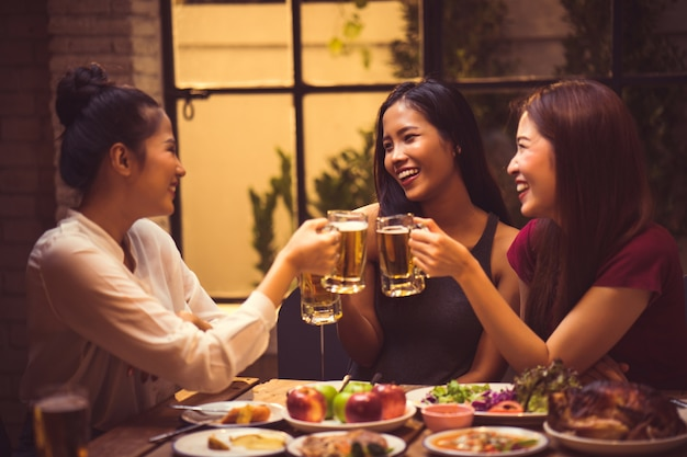 Las mujeres están bebiendo cerveza y las tintineo de vasos en un restaurante