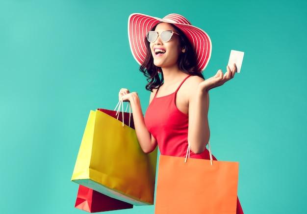 Las mujeres están de compras en el verano ella está usando una tarjeta de crédito y disfruta de las compras.