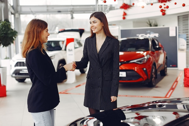 Mujeres con estilo y elegantes en un salón de autos