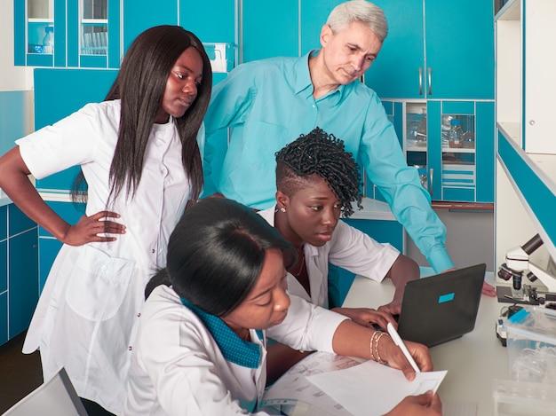 Las mujeres estudiantes de medicina africanas o graduados muestran datos al hombre caucásico, líder del grupo senor. buscando tratamiento, desarrollando una vacuna contra el virus corona que causa covid-19. informe de progreso en laboratorio.