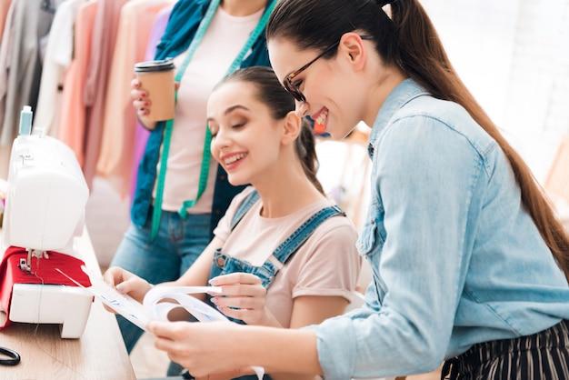 Mujeres en la fábrica de prendas de vestir una de ellas mostrando un plano.