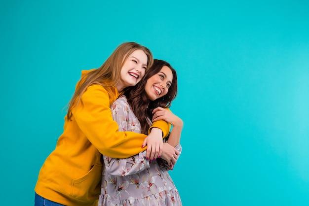 Mujeres felices abrazándose aisladas sobre fondo azul turquesa
