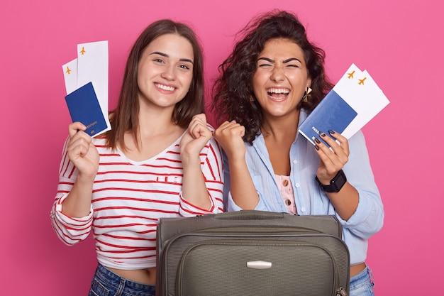 Mujeres felices apretando el puño como ganadores, sosteniendo pasaportes y boletos de embarque, vistiendo ropa de moda