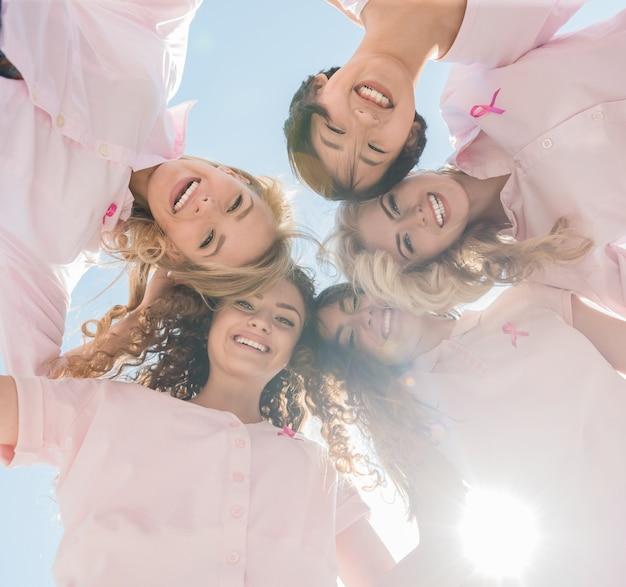 Mujeres felices en círculo con cintas de color rosa.