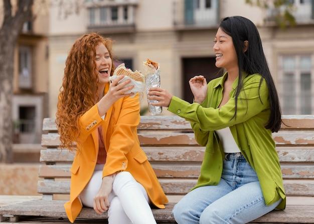 Mujeres felices comiendo juntos comida callejera