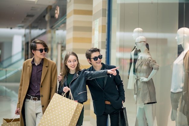 Mujeres felices de compras en el centro comercial y señalar con el dedo en el escaparate