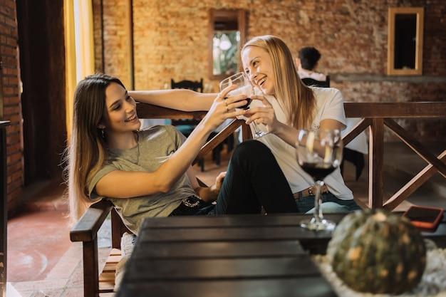 Mujeres felices con copas de vino hablan y ríen en un restaurante.