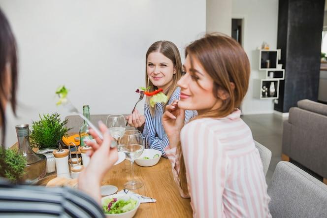 Mujeres felices en camisas comiendo