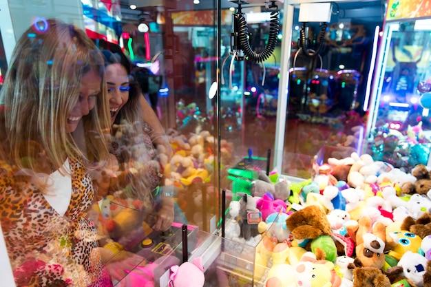 Mujeres felices jugando arcade machine