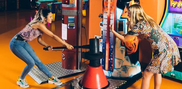 Mujeres felices jugando juego de arcade