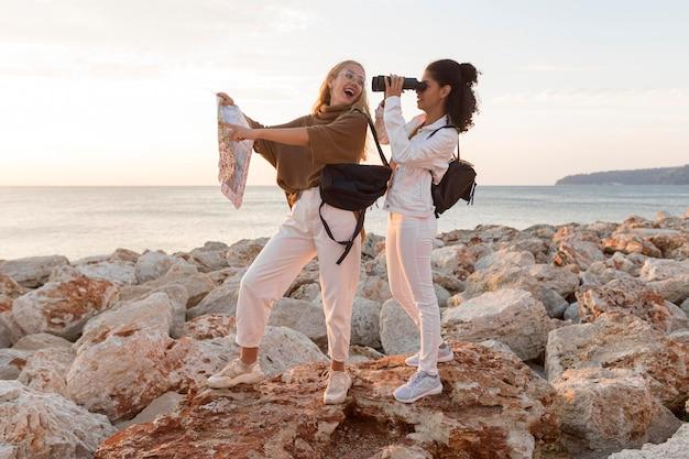 Mujeres felices con mapa y binoculares