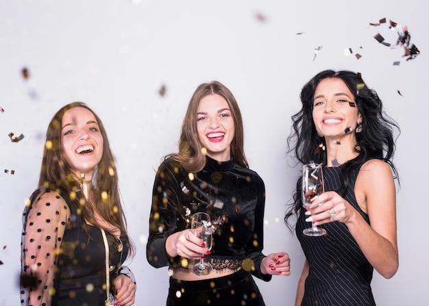 Mujeres felices de pie con copas de champán bajo lentejuelas
